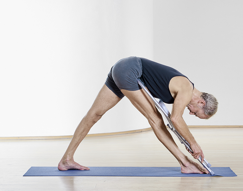 Yogapose mit Hilfsmittel Stuhl